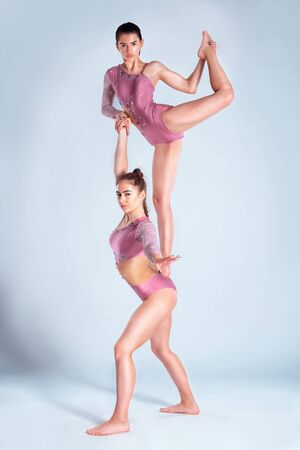 Photo pour Two flexible girls gymnasts in beige leotards performing complex elements of gymnastics using support, posing isolated on white background. Close-up. - image libre de droit