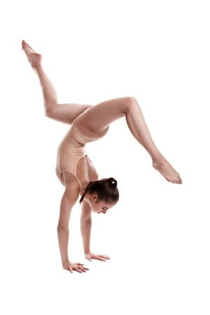 Photo pour Flexible girl gymnast in beige leotard is performing an exercise standing on her hands while posing isolated on white background. Close-up. - image libre de droit