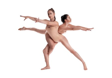 Photo pour Two flexible girls gymnasts in beige leotards are performing exercises using support and posing isolated on white background. Close-up. - image libre de droit