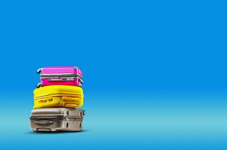Photo pour Three multicolored suitcases are lying on top of each other against a blue background. A realistic shadow is drawn in under them. Collage. Copy space for your text or images, close-up. - image libre de droit