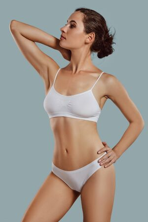 Foto de Young woman in white underwear, with bundled hair, posing in studio against gray background. Plastic surgery, aesthetic cosmetology. Close-up. - Imagen libre de derechos