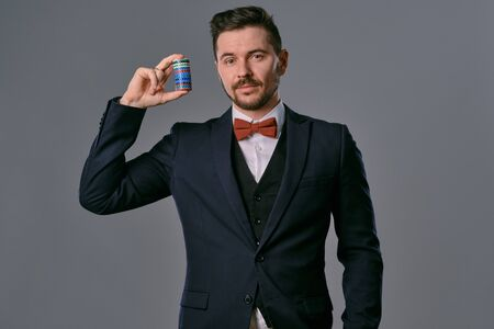 Photo for Man in black classic suit and red bow-tie showing some colored chips, posing against gray studio background. Gambling, poker, casino. Close-up. - Royalty Free Image