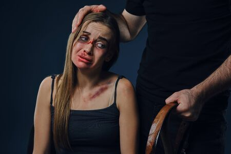 Photo pour Cruel man put his hand on female head, showing belt. Victim with bruises on face sitting nearby. Blue background. Domestic violence. Close-up. - image libre de droit