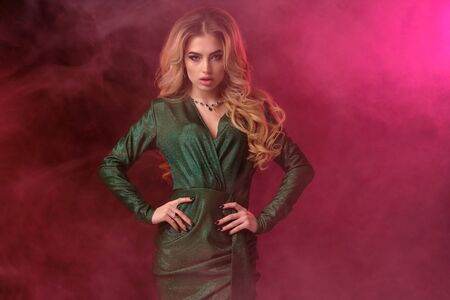 Photo pour Blonde curly woman in green stylish dress and jewelry. She has put her hands on waist, posing on colorful smoky background. Fashion, beauty. Close up - image libre de droit