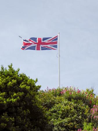 Union Jack flag flying over a blue sky background