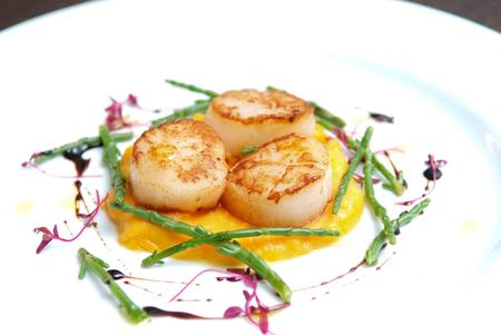 Photo pour Scallops, creatively arranged food on a white restaurant plate - image libre de droit