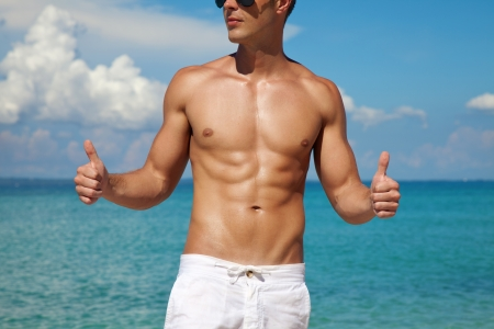 Foto de Muscular man showing thumbs up on a beach - Imagen libre de derechos