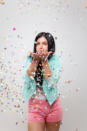 Young beautiful woman in party mood with confetti all around