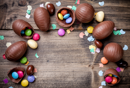 Photo pour Delicious chocolate easter eggs and sweets on wooden background - image libre de droit