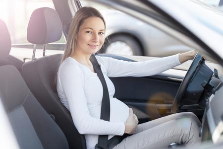 Photo pour Pregnant woman driving her car, wearing seat belt - image libre de droit