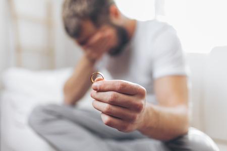 Photo pour Heartbroken man at home holding a wedding ring - image libre de droit