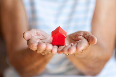 Photo pour Elderly woman holding a small house in her hands - image libre de droit