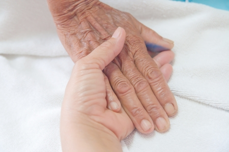 Photo pour A young hand touches and holds an old wrinkled hand  - image libre de droit