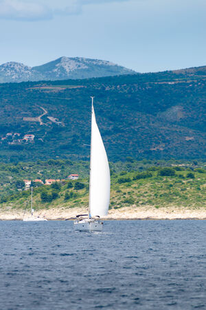 Yacht sailing in Adriatic sea near island with hills and mountains