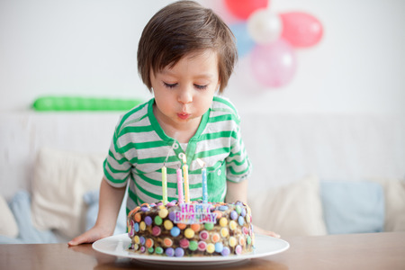Beautiful adorable four year old boy in green shirt, celebrating his birthday, blowing candles on homemade baked cake, indoor. Birthday party for kids