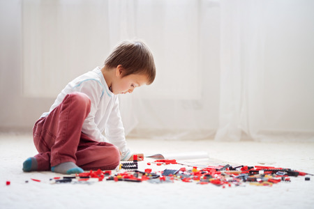 Foto de Little child playing with lots of colorful plastic blocks indoor, building a fire truck and a fire house, reading from a manual and imagining - Imagen libre de derechos