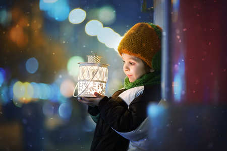 Photo pour Cute boy, holding lantern outdoor, wintertime - image libre de droit
