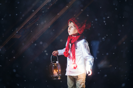 Sweet boy, holding a lantern, looking at a light coming through a window, standing in the snow, outdoors