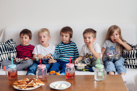 Five sweet kids, friends, sitting in living room at home, watching TV and eating popcorn