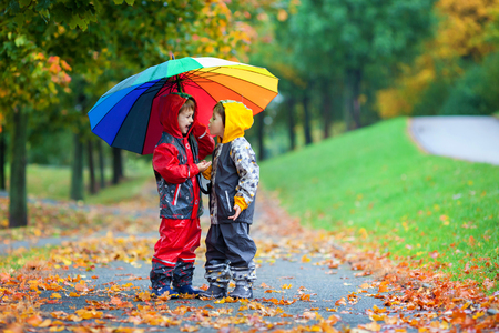 Two adorable children, boy brothers, playing in park with colorful rainbow umbrella on a rainy autumn dayの写真素材