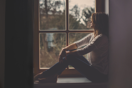 Photo pour Young attractive woman, sitting on a window, looking outside, lonely mood - image libre de droit