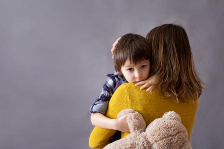 Photo pour Sad little child, boy, hugging his mother at home, isolated image, copy space. Family concept - image libre de droit