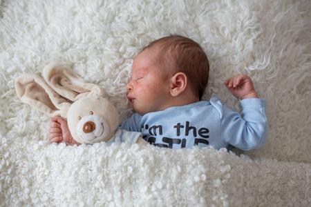 Foto de Little newborn baby sleeping with toy, baby with scin rash, child dermatitis symptom problem rash, newborn suffering atopic symptom on skin. concept child health - Imagen libre de derechos
