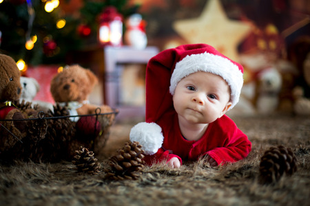 Foto de Portrait of newborn baby in Santa clothes in little baby bed, winter snow landscape outdoor - Imagen libre de derechos