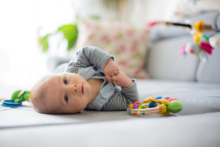Cute baby boy, playing with toys in a sunny living room, lying down on the sofa