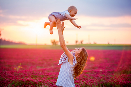 Photo pour Young mother holding her todller son in crimson clover field, family having fun togther - image libre de droit
