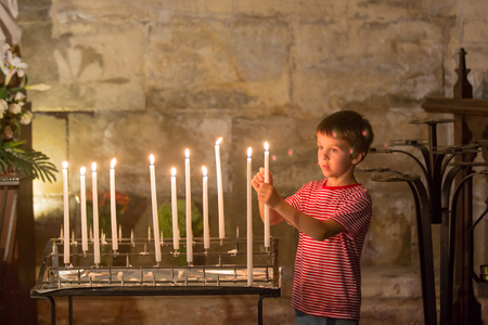 Little boy prays and puts a candle in Orthodox Church, sad kid with faith