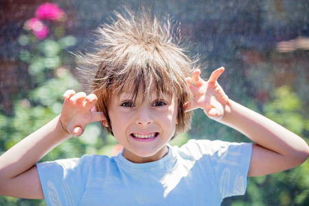 Foto de Cute little boy with static electricy hair, having his funny portrait taken outdoors on a trampoline - Imagen libre de derechos