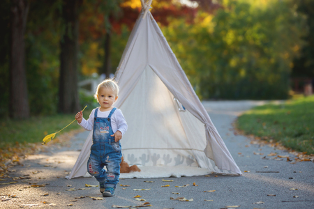 Photo pour Children, sitting in a tent teepee, holding teddy bear toy with a nature autumn background in the park, imagination or happiness concept - image libre de droit