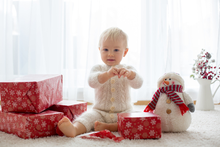 Foto de Cute toddler boy, sweet baby, opening presents at home, back lit - Imagen libre de derechos