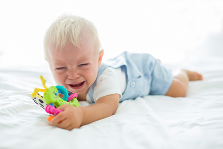 Foto de Toddler baby boy, playing with dummy, crying unhappy for the pacifier in children bedroom - Imagen libre de derechos