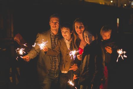 Foto de Waist up portrait of happy family celebrating New Year together and lighting sparklers outdoors in garden - Imagen libre de derechos