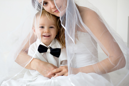 Portrait of elegant handsome little boyand mom as bride, lying in bedon her wedding day, dressed in bridal dress, baby with bow
