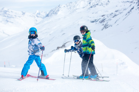 Foto de Happy people, children and adults, skiing on a sunny day in Tyrol mountains. Kids having fun while skiing - Imagen libre de derechos
