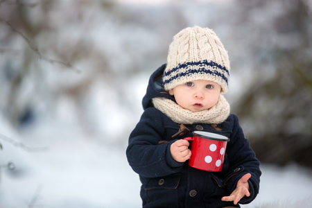 Foto de Sweet siblings, children having winter party in snowy forest. Kids friends rest outdoor at nature. Young brothers, boys, drinking tea from thermos. Hot drinks and beverage in cold weather - Imagen libre de derechos