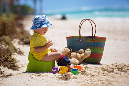 Photo for Little toddler boy, learning potty training on the beach on a tropical island Mauritius - Royalty Free Image