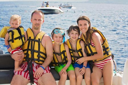 Foto de Happy family with life vests, having fun on a boat trip while on holiday in Mauritius - Imagen libre de derechos
