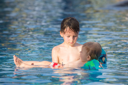 Photo pour Adorable happy little child, toddler boy, having fun relaxing and playing with his older brother in a pool on sunny day during summer vacation in resort - image libre de droit