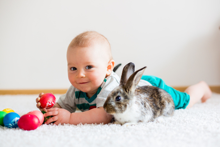 Foto de Little toddler child, baby boy, playing with bunnies and easter eggs at home, colorful hand drawings on the eggs - Imagen libre de derechos
