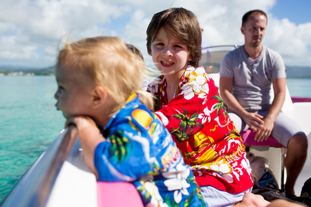 Photo pour Happy beautiful fashion family, children and parents, dressed in hawaiian shirts, enjoying day trip with speed boat in Mauritius - image libre de droit