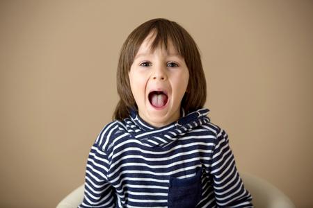 Photo pour Sweet preschool boy, making faces with different emotion, isolated image - image libre de droit