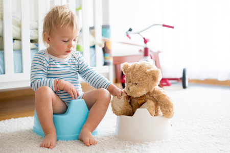 Photo pour Cute toddler boy, potty training, playing with his teddy bear on potty - image libre de droit