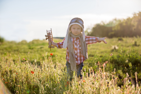 Photo pour Sweet toddler baby boy, child playing with airplane in poppy fiead, beautiful sunset on summer day - image libre de droit