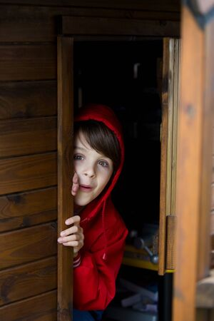 Preteen boy in red sweatshirt, hiding behind a wooden door, looking scared and sad