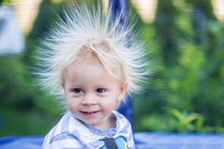 Photo pour Cute little boy with static electricy hair, having his funny portrait taken outdoors on a trampoline - image libre de droit