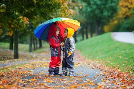 Foto de Two adorable children, boy brothers, playing in park with colorful rainbow umbrella on a rainy autumn day - Imagen libre de derechos